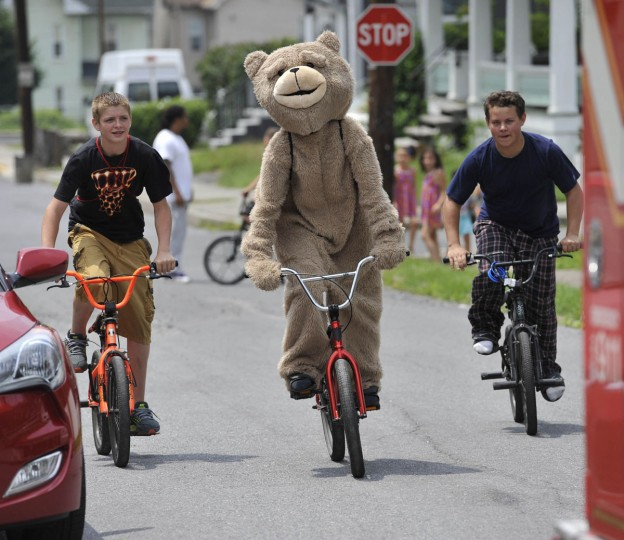 "Evan McGilvery, 13, of Johnstown, Pa., rides his bike with his friends, one of which portraying ""Ted 2"" as the youngsters head to check out a fire scene in Johnstown, Pa., Friday, July 3, 2015. (Todd Berkey/The Tribune-Democrat via AP)"