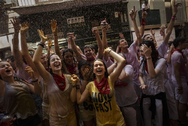 Revelers are sprayed with water as they celebrate during the launch of the 'Chupinazo' rocket, to celebrate the official opening of the 2015 San Fermin fiestas in Pamplona, Spain, Monday, July 6, 2015. (AP Photo/Daniel Ochoa de Olza)