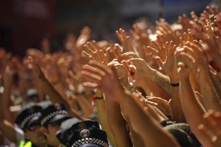 Revelers rise their arms as they celebrate during the launch of the 'Chupinazo' rocket, to celebrate the official opening of the 2015 San Fermin Fiestas, in Pamplona, northern Spain, Monday, July 6, 2015. (AP Photo/Alvaro Barrientos)
