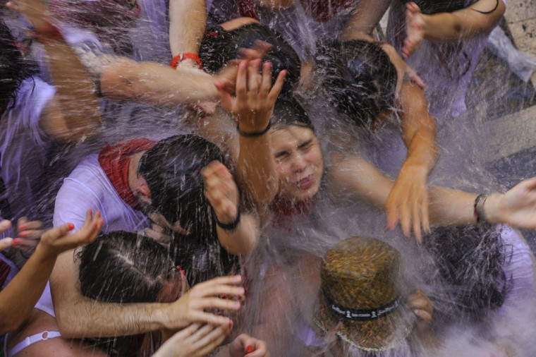 Revelers cool off with water thrown from a balcony during the launch of the 'Chupinazo' rocket, to celebrate the official opening of the 2015 San Fermin Fiestas, in Pamplona, northern Spain, Monday, July 6, 2015. (AP Photo/Alvaro Barrientos)