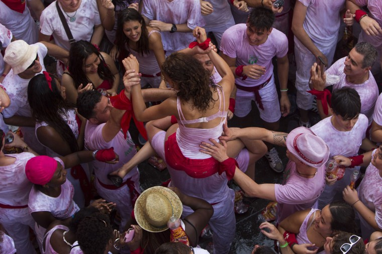 "A girl is held by other revelers during the launch of the ""Chupinazo"" rocket, to celebrate the official opening of the 2015 San Fermin fiestas in Pamplona, Spain, Monday, July 6, 2015. (AP Photo/Andres Kudacki)"