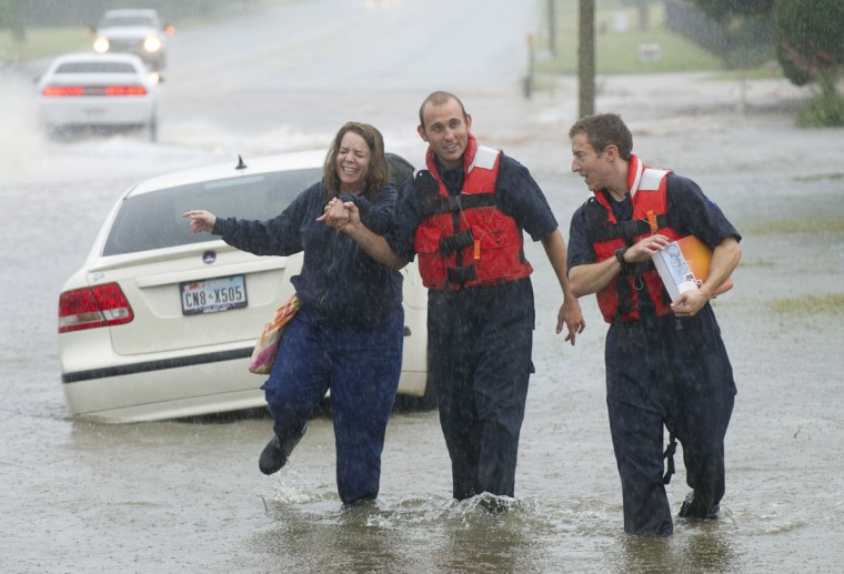 Firefighters Kendall Kohutek, center, and Seth Wilson, right, come to the rescue of stranded motorist Teresa McGuinness, left, on Antilley Road near Tamarisk Circle, Tuesday, July 7, 2015, in Abilene, Texas. (Nellie Doneva/The Abilene Reporter-News via AP)