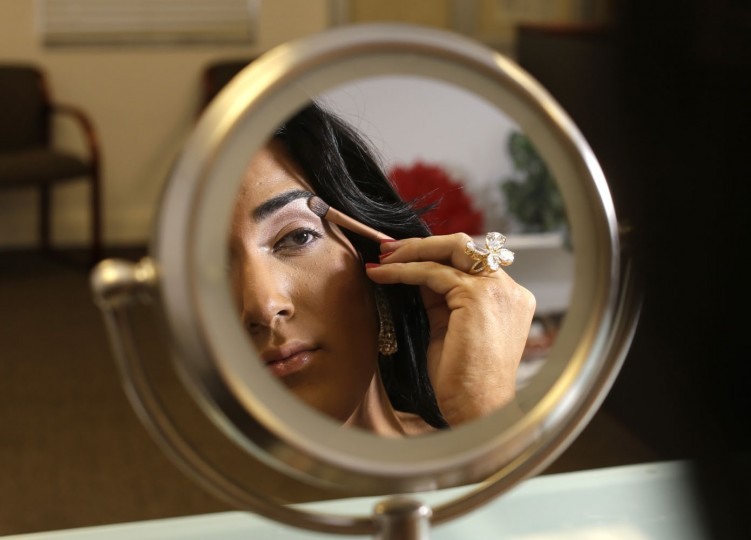 In this photo taken June 6, 2015, Andii Viveros, 21, of Davie, Fla., applies makeup as she prepares to host the annual Sun Serve LGBTQA Colors of the Wind youth prom in Fort Lauderdale, Fla. Viveros, who identifies as a transgender female, said she was always different from an early age growing up as a boy. Her parents accepted her to be anyway she wanted to be. She fought for her rights in high school, sometimes violating the school's code of conduct by wearing dresses. She was elected prom queen in high school and is now studying sociology in college. (AP Photo/Lynne Sladky)