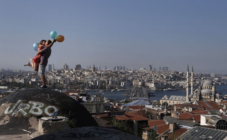 A couple kiss each other as they pose for a friend taking photographs, backdropped by Istanbul's skyline, Thursday, July 9, 2015. Istanbul is a thoroughly modern place, but it traces its roots back to 660 B.C. Itís the former seat of the opulent Byzantine and Ottoman empires and is divided into European and Asian sides by the Bosphorus Strait, offering a wealth of history and stunning scenery. (AP Photo/Emrah Gurel)