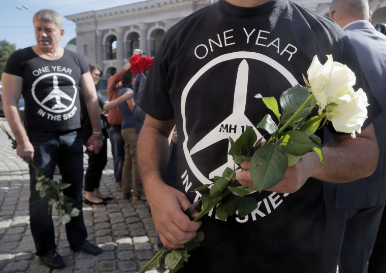 "Ukrainian lawmakers hold flowers as they offer them at the Netherlands Embassy for the Malaysia Airlines Flight MH17 crash victims, in Kiev, Ukraine, Friday, July 17, 2015. Residents of the Ukrainian village where the Malaysian airliner was shot down with 298 people aboard a year ago joined a procession to the crash site on Friday, while Australia's prime minister remembered the ""savagery"" of the disaster as he unveiled a plaque in Canberra that's set in soil from where the wreckage fell. (AP Photo/Efrem Lukatsky)"