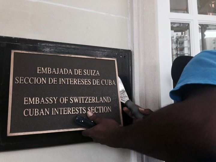 A worker the removes Cuban Interests Section sign in Washington, just days prior to the building being accredited as the Cuban Embassy. Cuba's blue, red and white-starred flag is set to fly Monday, July 20, outside the country's diplomatic mission in the United States for the first time since the countries severed ties in 1961. (AP Photo/Bill Gorman, File)