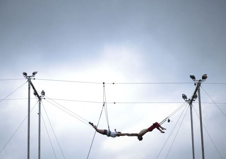 Darren Rabinowitz, right, a flying trapeze instructor for Aerial Trapeze, grasps a swinger during Floyd Fest on Thursday, July 23, 2015, in Floyd, Va. The five-day festival has nine stages and is hosting nearly 75 bands. (John Roark/The Roanoke Times via AP)