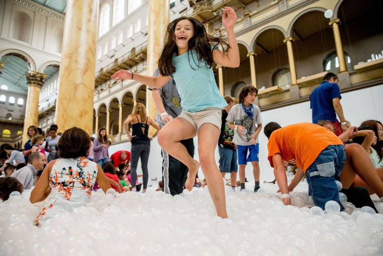 "Ilana Cohen, 9, of Alexandria, Va., jumps into a sea of plastic balls at ""The Beach"", an interactive architectural installation inside the National Building Museum in Washington, Friday, July 17, 2015. The Beach, which spans the length of the museum's Great Hall, was created in partnership with Snarkitecture, and covers 10,000 square feet and includes an ìoceanî of nearly one million recyclable translucent plastic balls. (AP Photo/Andrew Harnik)"
