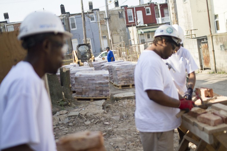 A city worker checks in on the progress and workers at the Details deconstruction site in the 900 block of N. Port Street. (Kalani Gordon, Baltimore Sun)