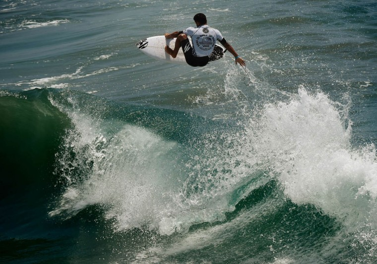 Professional surfer Michael Rodrigues of Brazil gets some air as he competes during his round two men's heat of the US Open of Surfing in Huntington Beach, California on July 29, 2015. The event celebrates it's 56th year beside the historic Huntington Pier which is considered the birthplace of California's surfing culture. (Mark Ralston/Getty Images)