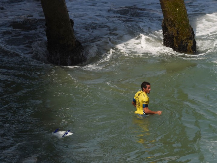 Professional surfer Ramzi Boukhiam of Morocco leaves the water with his broken board after his round two men's heat of the US Open of Surfing in Huntington Beach, California on July 29, 2015. The event celebrates it's 56th year beside the historic Huntington Pier which is considered the birthplace of California's surfing culture. (Mark Ralston/Getty Images)