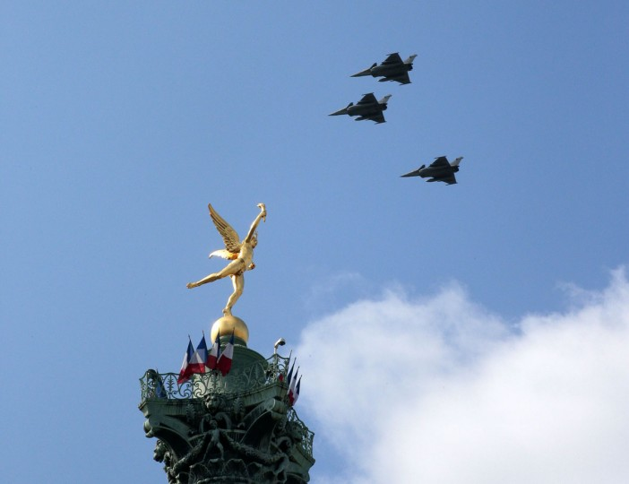 Three French Air Force strategic unit Rafale B fighter jets fly over the July Column and its angel statue on the Place de la Bastille during the annual Bastille Day military parade in Paris on July 14, 2015. (JACQUES DEMARTHON/AFP/Getty Images)