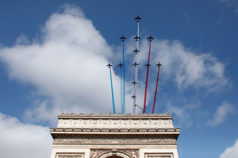 Twelve alphajets of the French Air Force Acrobatic Patrol, the Patrouille de France, fly over the Arc de Triomphe monument in their Lorraine Cross formation, during the annual Bastille Day military parade in Paris on July 14, 2015. (THIBAULT CAMUS/AFP/Getty Images)
