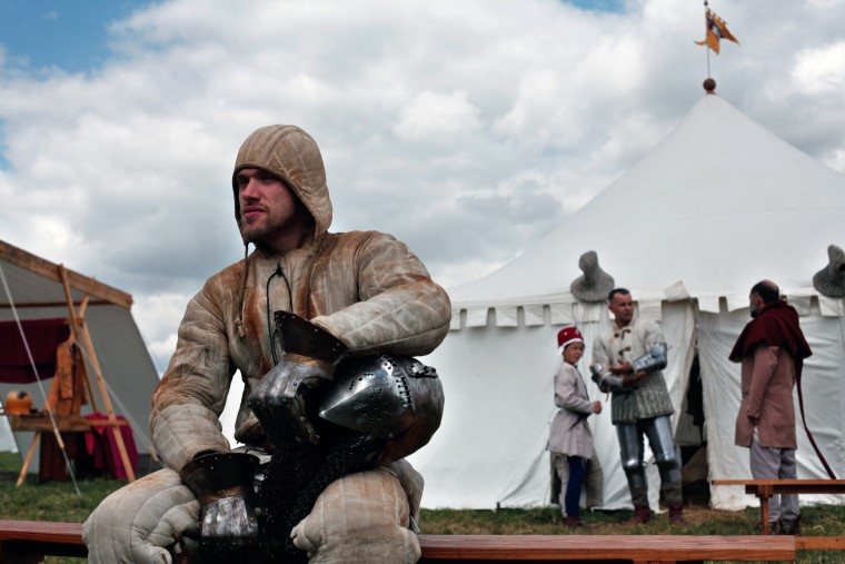 A man wearing a Medieval grab rests during a reenactment of the Battle of Agincourt, in Agincourt, northern France, Saturday, July 25, 2015. The French are hosting a reenactment of the clash with England this weekend. More than 800 people in Medieval garb are gathering at the site to commemorate the battle, which was a turning point in the Hundred Years' War. (Associated Press/Thibault Camus)