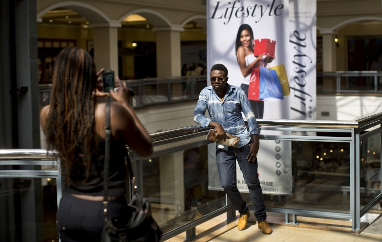 Ted Odhiambo, who said he used to work in one of the mall's shops, poses while his friend takes a photograph of him in the reopened Westgate Shopping Mall, nearly two years after a terrorist attack there left at least 67 people dead, in the capital Nairobi, Kenya Saturday, July 18, 2015. Hundreds of shoppers thronged through the reopened mall Saturday, following two years of repairs after security forces battled four gunmen from Somalia's al-Qaida-linked al-Shabab militant group there in September 2013. (/Ben Curtis/Associated Press)