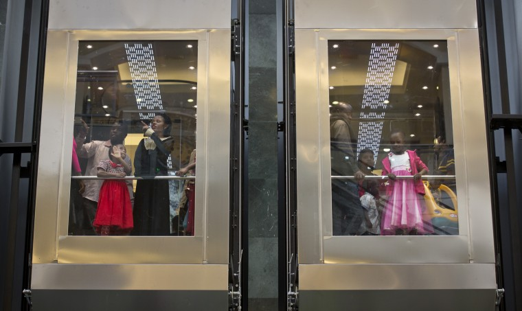 Shoppers look out through glass elevators in the reopened Westgate Shopping Mall, nearly two years after a terrorist attack there left at least 67 people dead, in the capital Nairobi, Kenya Saturday, July 18, 2015. Hundreds of shoppers thronged through the reopened mall Saturday, following two years of repairs after security forces battled four gunmen from Somalia's al-Qaida-linked al-Shabab militant group there in September 2013. (Ben Curtis/Associated Press)