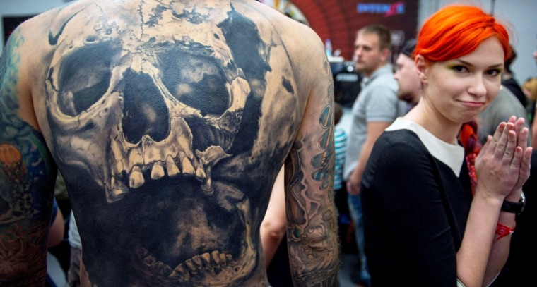 A woman reacts next to a man's tattooed back depicting a skull, during the Moscow International Tattoo Week in Moscow on July 25, 2015. (Alexander Utkin/AFP-Getty Images)