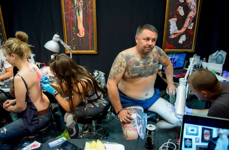 Tattoo artists work during the Moscow International Tattoo Week in Moscow on July 25, 2015. (Alexander Utkin/AFP-Getty Images)