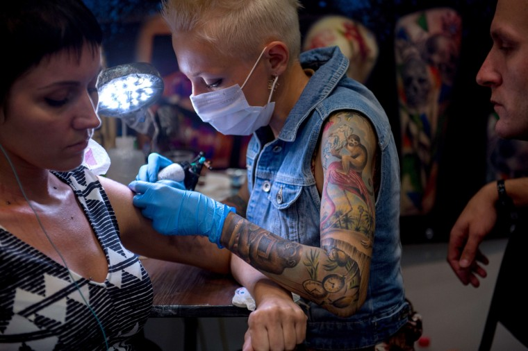 A tattoo artist works during the Moscow International Tattoo Week in Moscow on July 25, 2015. (Alexander Utkin/AFP-Getty Images)