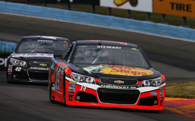 Tony Stewart, driver of the #14 Bass Pro Shops/Mobil 1 Chevrolet, leads Landon Cassill, driver of the #40 Hillman Automotive & Tire Chevrolet, during qualifying for the NASCAR Sprint Cup Series Cheez-It 355 at Watkins Glen International on August 8, 2015 in Watkins Glen, New York. (Jonathan Ferrey/Getty Images)