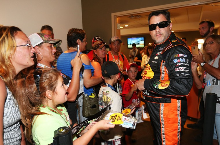 Tony Stewart, driver of the #14 Bass Pro Shops/Mobil 1 Chevrolet, signs autographs prior to the NASCAR Sprint Cup Series Cheez-It 355 at the Glen at Watkins Glen International on August 9, 2015 in Watkins Glen, New York. (Todd Warshaw/Getty Images)