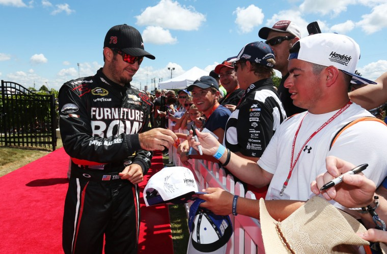 Martin Truex Jr., driver of the #78 Furniture Row/Visser Precision Chevrolet, signs autographs prior to the NASCAR Sprint Cup Series Cheez-It 355 at the Glen at Watkins Glen International on August 9, 2015 in Watkins Glen, New York. (Todd Warshaw/Getty Images)