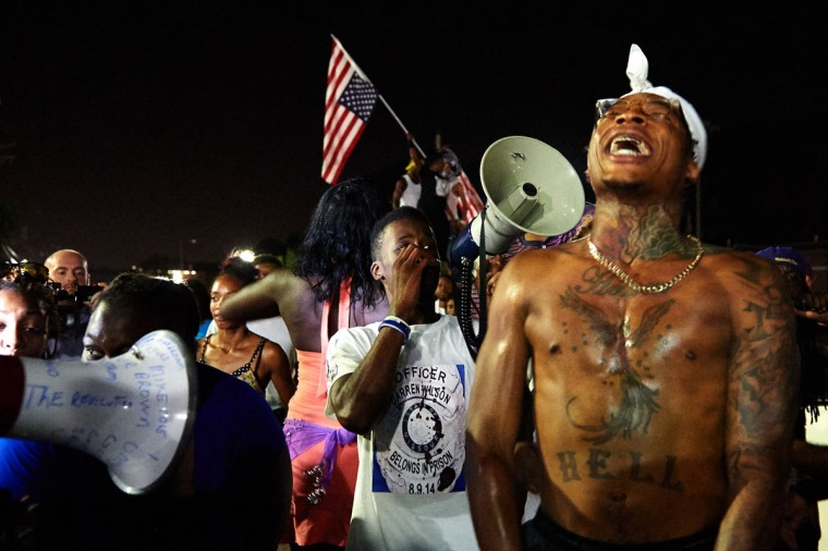 Protestors demonstrate outside the Ferguson Police Department in Ferguson, Missouri on August 7, 2014. As the embattled community celebrates the one year anniversary of the shooting of Michael Brown Jr. by a Ferguson police officer, there are a wide range of social events and civil disobedience actions throughout the St. Louis, Missouri area. (AFP Photo/Michael Thomasmichael b. thomas)