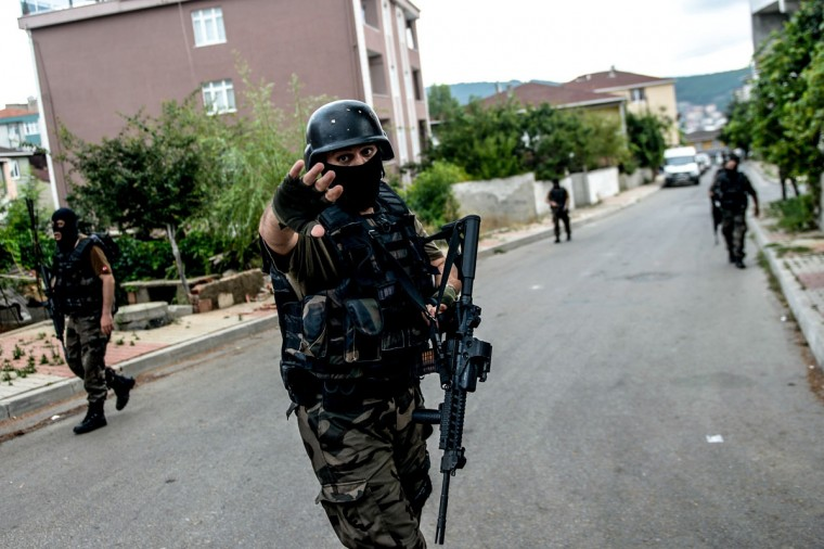 Turkish special force police officers take cover during clashes with attackers on August 10, 2015 at the Sultanbeyli district in Istanbul. Turkey's largest city Istanbul was Monday shaken by twin attacks on the US consulate and a police station as tensions spiral amid the government's air campaign against Kurdish militants. (AFP Photo/Ozan Kose)