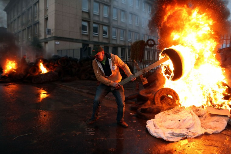 A man prepares to throw an burning tire as farmers protest in front of the prefecture early on August 19, 2015 in Saint-Lo, northwestern France. (AFP Photo/Charly Triballeau)