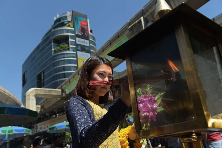 A woman lights incense sticks before offering prayers at the reopened Erawan shrine in Bangkok on August 19, 2015. Thai monks led prayers on August 19 for the reopening of Bangkok shrine where a blast killed 20 people, as police hunted a man shown on security footage calmly planting what is believed to be the bomb. (AFP Photo/Christophe Archambault)