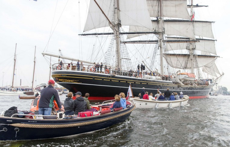 Motor boats and tall sailing ships sail from Ijmuiden towards Amsterdam, the Netherlands, on August 19, 2015, to join a parade of ships during the five-yearly nautical event Sail 2015. (JERRY LAMPEN/AFP/Getty Images)