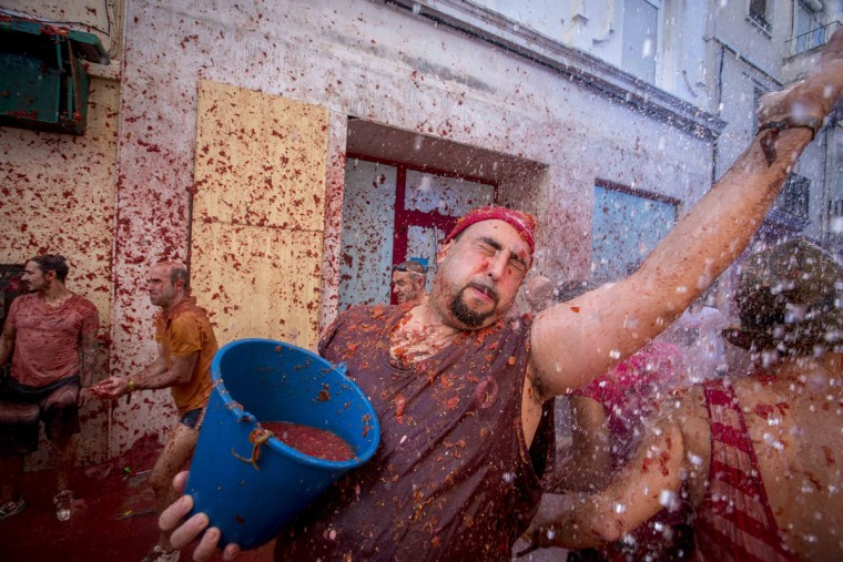 "A reveler holds a bucket of tomato pulp during the annual ""tomatina"" festivities in the village of Bunol, near Valencia on August 26, 2015. Some 22,000 revelers hurled 150 tons of squashed tomatoes at each other drenching the streets in red in a gigantic Spanish food fight marking the 70th annual ""Tomatina"" battle. (AFP Photo/Biel Alino)"