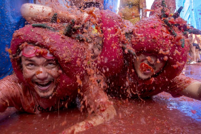 """Revelers slide around in tomato pulp during the annual """"tomatina"""" festivities in the village of Bunol, near Valencia on August 26, 2015. Some 22,000 revelers hurled 150 tons of squashed tomatoes at each other drenching the streets in red in a gigantic Spanish food fight marking the 70th annual """"Tomatina"""" battle. (AFP Photo/Biel Alino)"""