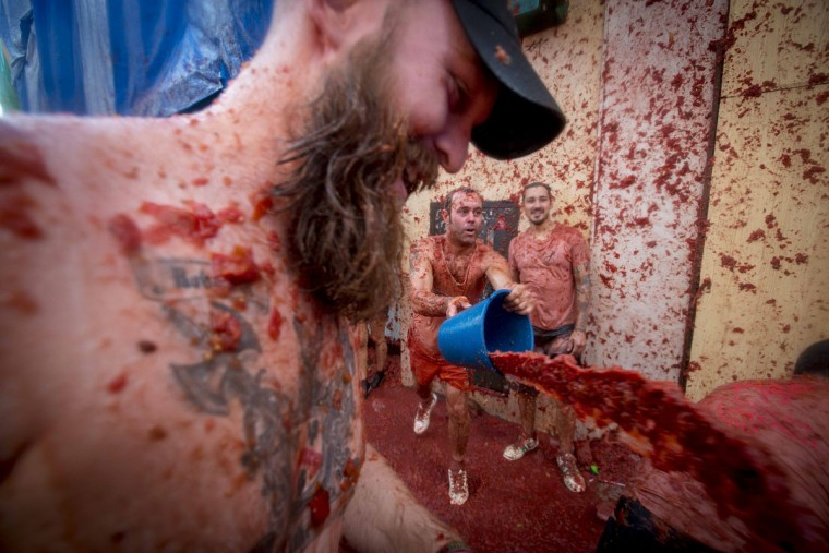 """A reveler throws a bucket of tomato pulp during the annual """"tomatina"""" festivities in the village of Bunol, near Valencia on August 26, 2015. Some 22,000 revelers hurled 150 tons of squashed tomatoes at each other drenching the streets in red in a gigantic Spanish food fight marking the 70th annual """"Tomatina"""" battle. (AFP Photo/Biel Alino)"""