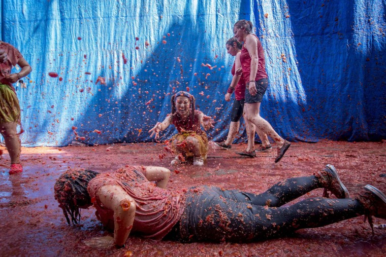 """Revelers throw tomato pulp at each other during the annual """"tomatina"""" festivities in the village of Bunol, near Valencia on August 26, 2015. Some 22,000 revelers hurled 150 tons of squashed tomatoes at each other drenching the streets in red in a gigantic Spanish food fight marking the 70th annual """"Tomatina"""" battle. (AFP Photo/Biel Alino)"""