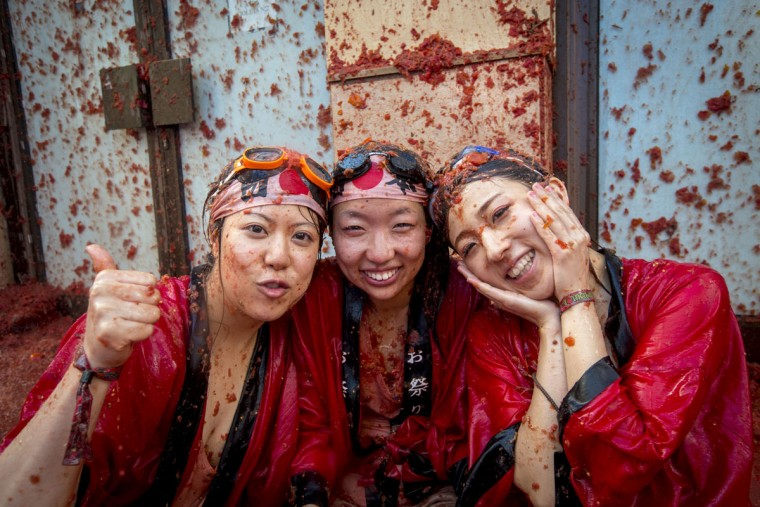 "Revelers covered in tomato pulp pose during the annual ""tomatina"" festivities in the village of Bunol, near Valencia on August 26, 2015. Some 22,000 revelers hurled 150 tons of squashed tomatoes at each other drenching the streets in red in a gigantic Spanish food fight marking the 70th annual ""Tomatina"" battle. (AFP Photo/Biel Alino)"