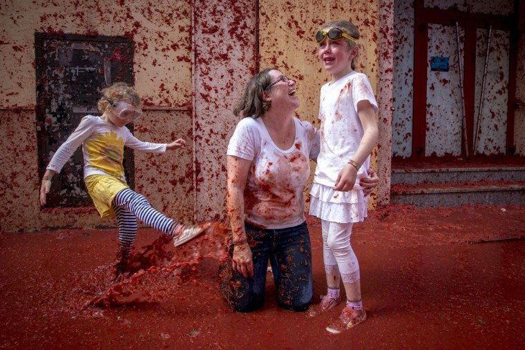"""A woman comforts a crying child covered in tomato pulp during the annual """"tomatina"""" festivities in the village of Bunol, near Valencia on August 26, 2015. Some 22,000 revelers hurled 150 tons of squashed tomatoes at each other drenching the streets in red in a gigantic Spanish food fight marking the 70th annual """"Tomatina"""" battle. (AFP Photo/Biel Alino)"""