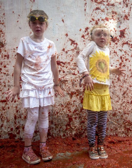 "Two children stand covered in tomato pulp during the annual ""tomatina"" festivities in the village of Bunol, near Valencia on August 26, 2015. (AFP Photo/Biel Alino)"