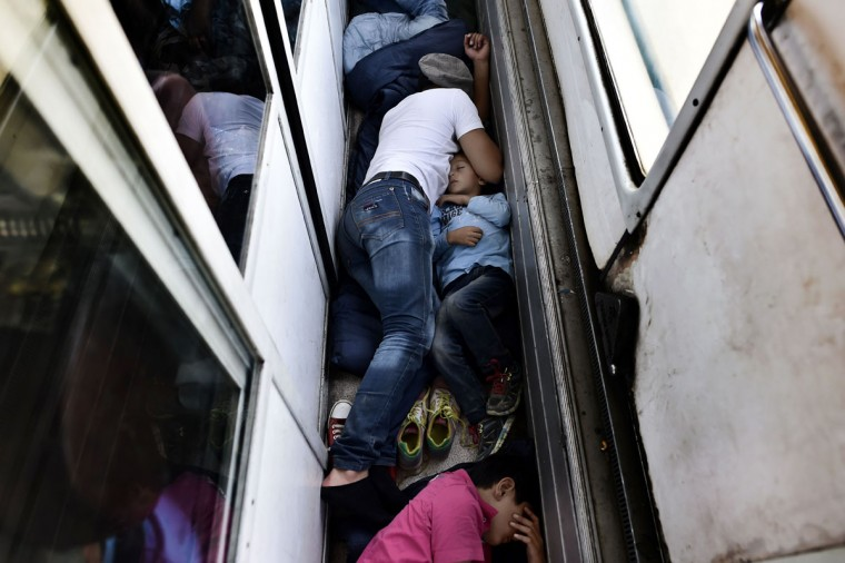 Syrian refugees and migrants sleep on the floor of a carriage as they travel on a train taking them from Macedonia (Also referred to as the Former Yugoslav Republic of Macedonia) to the Serbian border, on August 30, 2015. The EU is grappling with an unprecedented influx of people fleeing war, repression and poverty in what the bloc has described as its worst refugee crisis in 50 years. (AFP Photo/Aris Messinis)