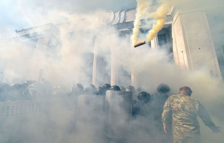 """Smoke rises from the parliament building in Kiev as activists of radical Ukrainian parties, including the Ukrainian nationalist party Svoboda (Freedom), clash with police officers on August 31, 2015. At least 20 were wounded in clashes outside parliament in Kiev after lawmakers gave initial approval to constitutional changes granting more autonomy to pro-Russian separatists in eastern Ukraine. A loud blast was heard outside parliament shortly after the bill was passed, an AFP journalist said. Ukrainian interior ministry advisor and top lawmaker Anton Gerashchenko wrote on Facebook that attackers threw a hand grenade at National Guard troops guarding the building in what he called an """"act of provocation."""" (AFP Photo/Sergei Supinsky)"""