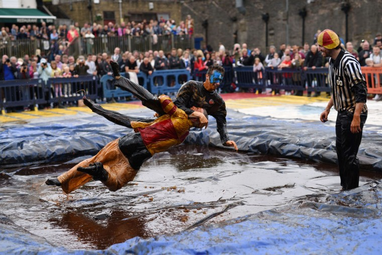 Competitors take part in the 8th annual World Gravy Wrestling Championships at the Rose n Bowl Pub in Bacup, north west England on August 31, 2015. Contestants must participate in fancy dress and wrestle in a pool of Lancashire Gravy for 2 minutes whilst being scored for a variety of wrestling moves. (AFP Photo/Oli Scarff)
