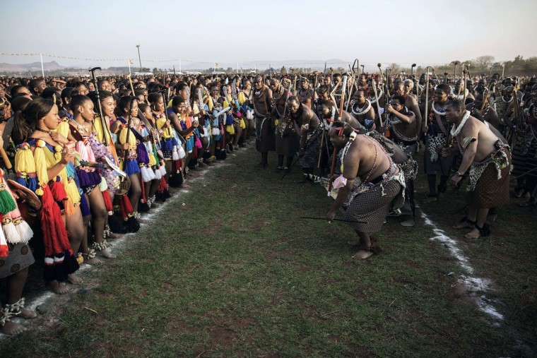 King Mswati III of Swaziland (2nd R) kneels down in atraditional show of appreciation for the maidens as they sing and dance on the last day of the annual royal Reed Dance at the Ludzidzini Royal palace on August 31, 2015 in Lobamba, Swaziland. Umhlanga, or Reed Dance ceremony, is an annual Swazi cultural event where tens of thousands of Swazi girls travel from the various chiefdoms to the Ludzidzini Royal Village to participate in the eight-day event. The Reed Dance is a beauty pageant at which King Mswati III can choose a new wife from one of tens of thousands of young virgins who come to dance before him. (AFP Photo/Gianluigi Guercia)