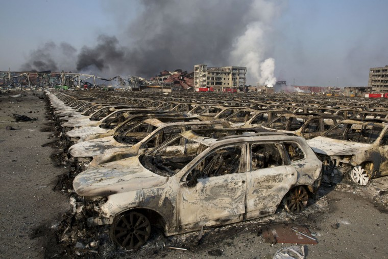 Smoke billows from the site of an explosion that reduced a parking lot filled with new cars to charred remains at a warehouse in northeastern China's Tianjin municipality, Thursday, Aug. 13, 2015. Huge, fiery blasts at a warehouse for hazardous chemicals killed many people and turned nearby buildings into skeletal shells in the Chinese port of Tianjin, raising questions Thursday about whether the materials had been properly stored. (AP Photo/Ng Han Guan)