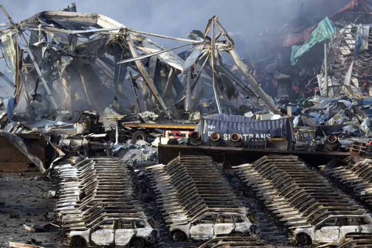 Charred remains of a warehouse and new cars are left burned after an explosion at a warehouse in northeastern China's Tianjin municipality, Thursday, Aug. 13, 2015. Huge, fiery blasts at a warehouse for hazardous chemicals killed many people and turned nearby buildings into skeletal shells in the Chinese port of Tianjin, raising questions Thursday about whether the materials had been properly stored. (AP Photo/Ng Han Guan)