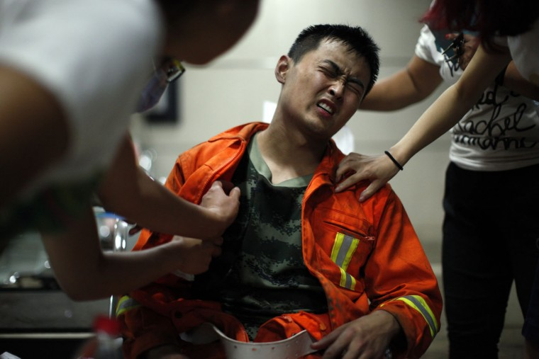 An injured firefighter grimaces as he is examined in a hospital following explosions in northeastern China's Tianjin municipality, Thursday, Aug. 13, 2015. Chinese state media reported huge explosions at the Tianjin port late Wednesday. (Chinatopix Via AP)