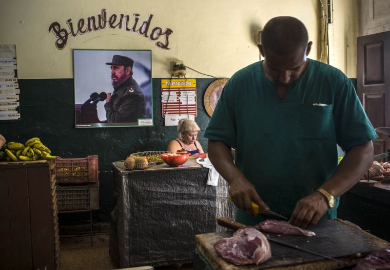 An image of Fidel Castro hangs under a welcome message, in a butcher shop in Havana, Cuba, Thursday, Aug. 13, 2015. Castro marked his 89th birthday Thursday, with a newspaper column repeating assertions that the U.S. owes socialist Cuba ìnumerous millions of dollarsî for damages caused by a decades-long embargo. (AP Photo/Ramon Espinosa)