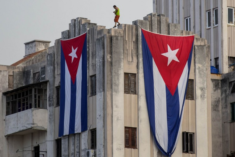 A man walks along the ledge of a building after hanging two giant Cuban flags, next to the US embassy, in Havana, Cuba. The embassy will hold a ceremony on Friday, Aug. 14, to raise the U.S. flag, to mark its reopening on Havanaís historic waterfront. (AP Photo/Ramon Espinosa)
