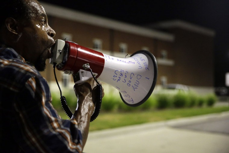 Protester Mo Brown yells into a megaphone outside the Ferguson Police Department, Friday, Aug. 7, 2015, in Ferguson, Mo. Sunday will mark one year since Michael Brown was shot and killed by Ferguson police officer Darren Wilson. (AP Photo/Jeff Roberson)