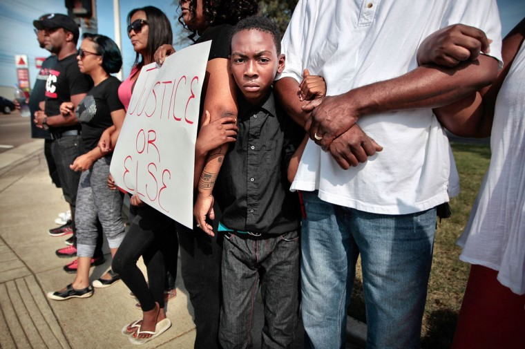 Isaiah Simpson, center, links arms with demonstrators during a Black Lives Matter rally, Sunday, Aug. 9, 2015, in Memphis, Tenn. The rally was held near where a Memphis Police officer shot and killed Darrius Stewart during a traffic stop on Friday, July 17, 2015. Members of the New Directions Church and Mid-South Peace and Justice Center joined the rally to mark the one-year anniversary of the shooting of Michael Brown by a police officer in Ferguson, Mo. (Jim Weber/The Commercial Appeal via AP)