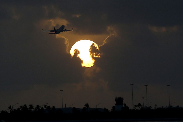 A plane takes off from Key West International Airport as the sun rises, Thursday, Aug. 6, 2015, in Key West, Fla. (AP Photo/Julio Cortez)